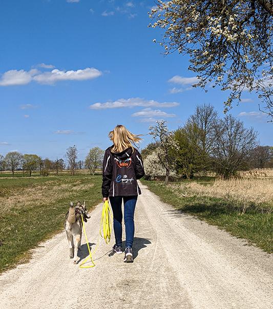Ellie und ich gehen zusammen über einen sandigen Weg. Auf meiner Jacke ist mein Logo zu sehen.