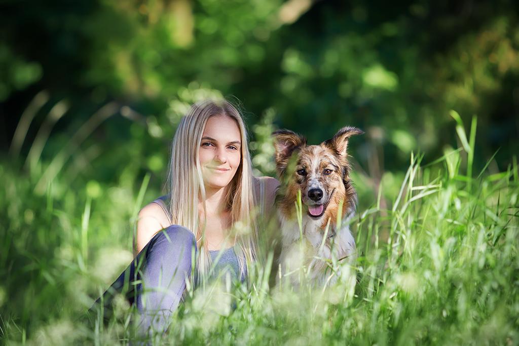 Ein blondes Mädchen sitzt mit ihrem Australian Shepherd im hohen Gras und schaut in die Kamera.