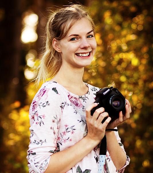 Das bin ich! Eine junge blonde Frau mit blauen Augen, die ihre Kamera in der Hand hält.