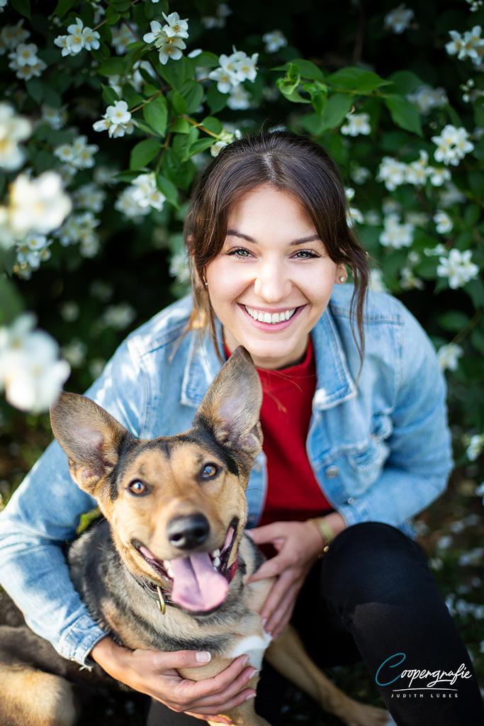 Hund und Mensch lachen in die Kamera beim Fotoshooting in der Blumenwiese